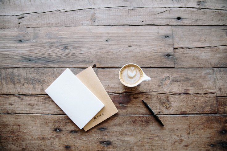 coffee and notepad on wooden table.jpg