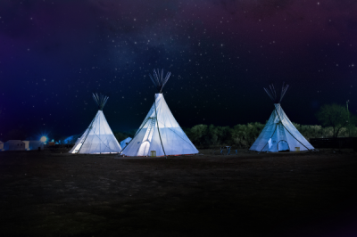 3 modern teepees lit up inside at night under the stars
