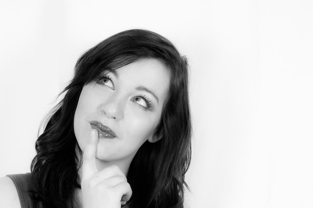 woman with fingertip to mouth looking up like she is thinking